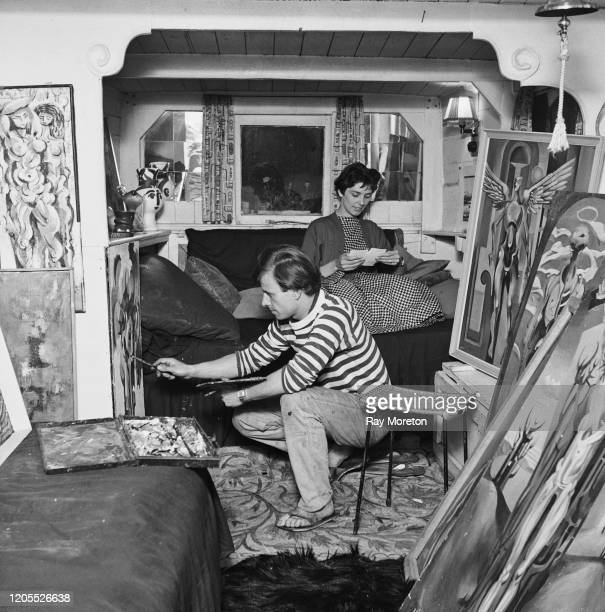 Artist Derek Jukes working on a painting on his houseboat 'Coot' moored on the Thames by Cheyne Walk Chelsea London September 1959