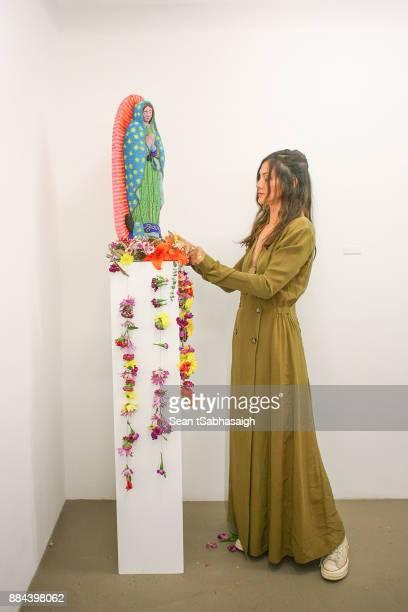 Artist Diana Garcia poses for a photo in front of her artwork atOptiMystic A Brandon Boyd Pop Up Gallery Featuring He Tasya Van Ree Natalie Bergman...