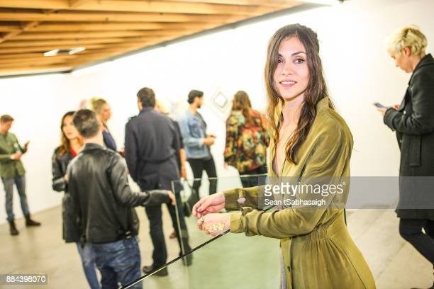 Artist Diana Garcia poses for a photo in front of her artwork at OptiMystic A Brandon Boyd Pop Up Gallery Featuring He Tasya Van Ree Natalie Bergman...
