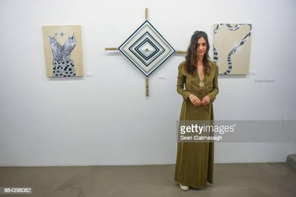 Artist Diana Garcia poses in front of her artwork at OptiMystic A Brandon Boyd Pop Up Gallery Featuring He Tasya Van Ree Natalie Bergman Diana Garcia...
