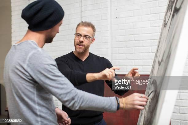artist discussing drawing with man in studio - kunsthändler stock-fotos und bilder