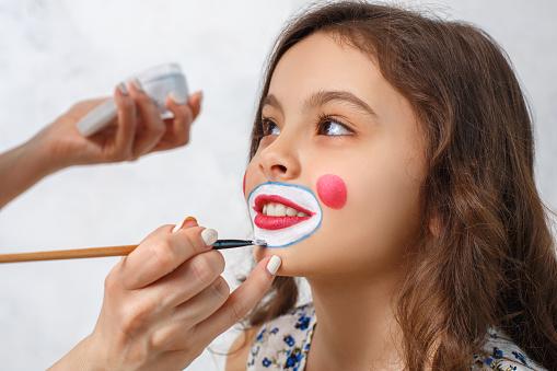 Artist doing clown makeup for a little girl 841515560