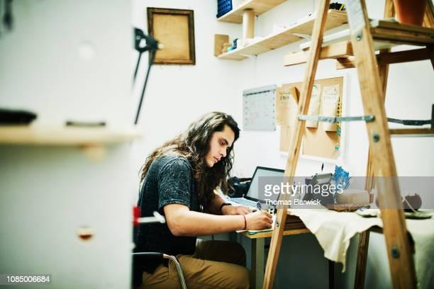 Artist doing paperwork at desk in studio
