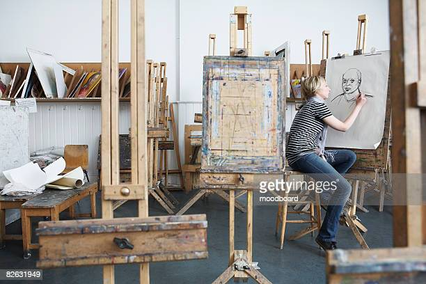 Artist drawing charcoal portrait among easels in studio