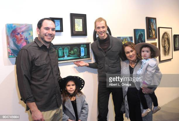 Artist Eric Gonzales and family pose with actor Doug Jones at Guillermo Del Toro's Art Show In The Name Of The Monster The Robot And The Bleeding...