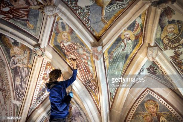 artist examining old paintings in antique catholic church - stock photo - restoration style stock pictures, royalty-free photos & images