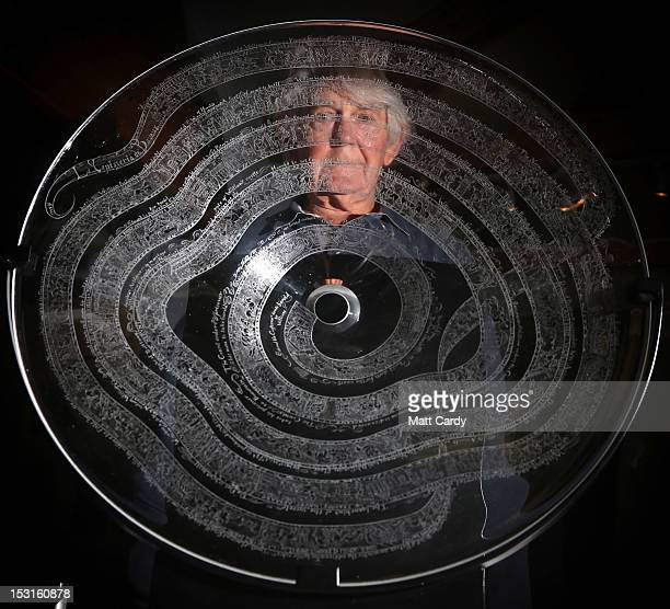 Artist Frank Grenier looks through a glass bowl which has been engraved with a recreation of the Bayeux Tapestry on October 1 2012 in Glastonbury...
