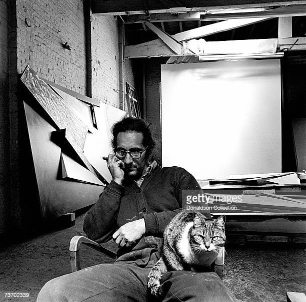Artist Frank Stella poses with his cat at his studio in 1975 in New York