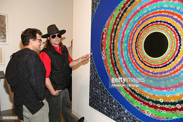 """Artist Fred Tomaselli and actor Val Kilmer look at Tomaselli's piece """"Big Eye"""" at Art Basel Miami at the Miami Beach Convention Center on December 4,..."""