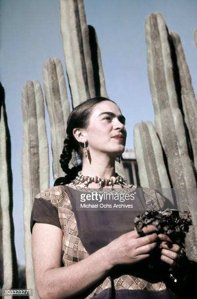 Artist Frida Kahlo poses for a portrait at the home and studio she shares with her husband Diego Rivera designed by architect Juan O'Gorman circa...