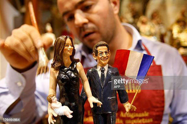 Artist Gennaro di Virgilio applies the finishing touches to Christmas figurines depicting French President Nicolas Sarkozy and his wife Carla Bruni...