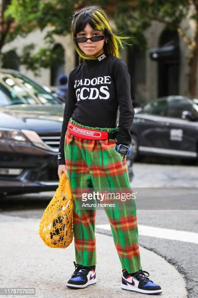 Artist Giana is seen wearing black GCD sweatshirt green The Animal Observatory plaid pants yellow Tuza Store Mexico bag red Supreme belt and black...