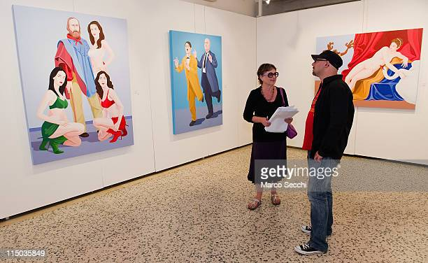 Artist Giuseppe Veneziano is interviewed in front of three of his works by Franca Urbani at Galleria Contini on June 1 2011 in Venice Italy
