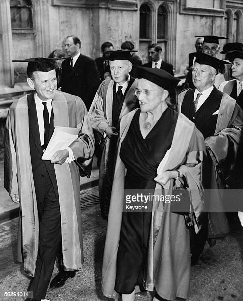 Artist Graham Sutherland walking with Cambridge Fellow Helen Maud followed by actor Charlie Chaplin and Yehudi Menuhin wearing caps and gowns as they...