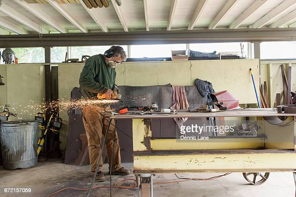 Artist grinding steel in workshop