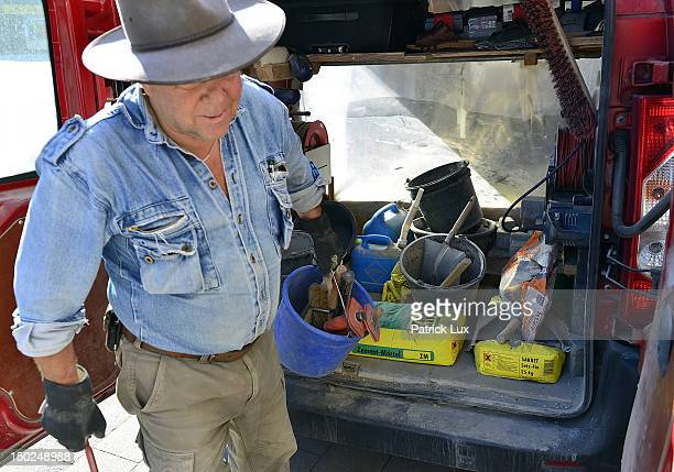 Artist Gunter Demnig gets his tools from his car for laying 'Stolpersteine' memorial cobblestones outside a residence on August 13, 2012 in Hamburg,...