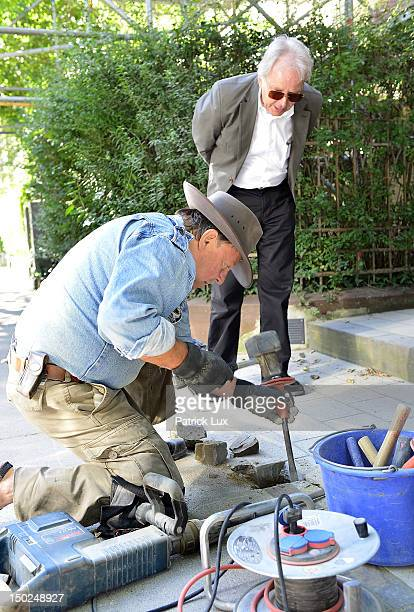 Artist Gunter Demnig lays 'Stolpersteine' memorial cobblestones outside a residence together with Peter Hess, the Hamburgian coordinator for the...