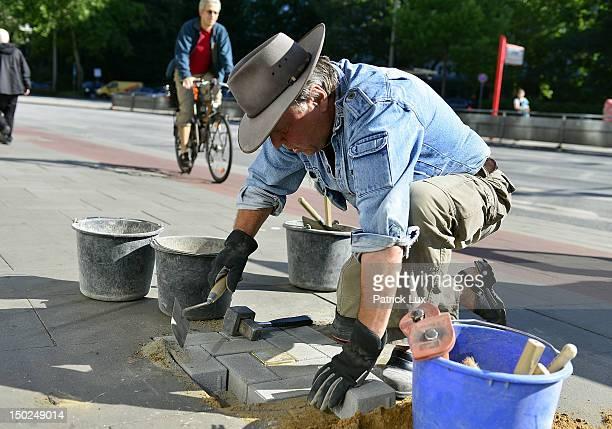 Artist Gunter Demnig lays 'Stolpersteine' memorial cobblestones outside a residence on August 13, 2012 in Hamburg, Germany. Each stone has a brass...