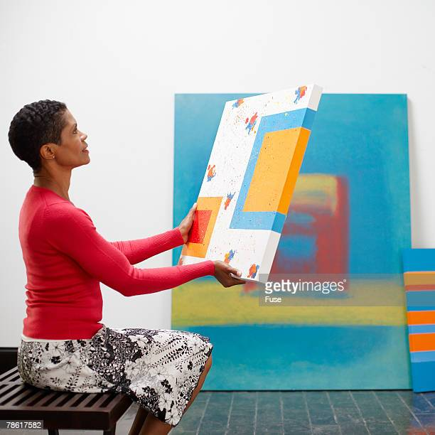 Artist Hanging Paintings at Exhibition