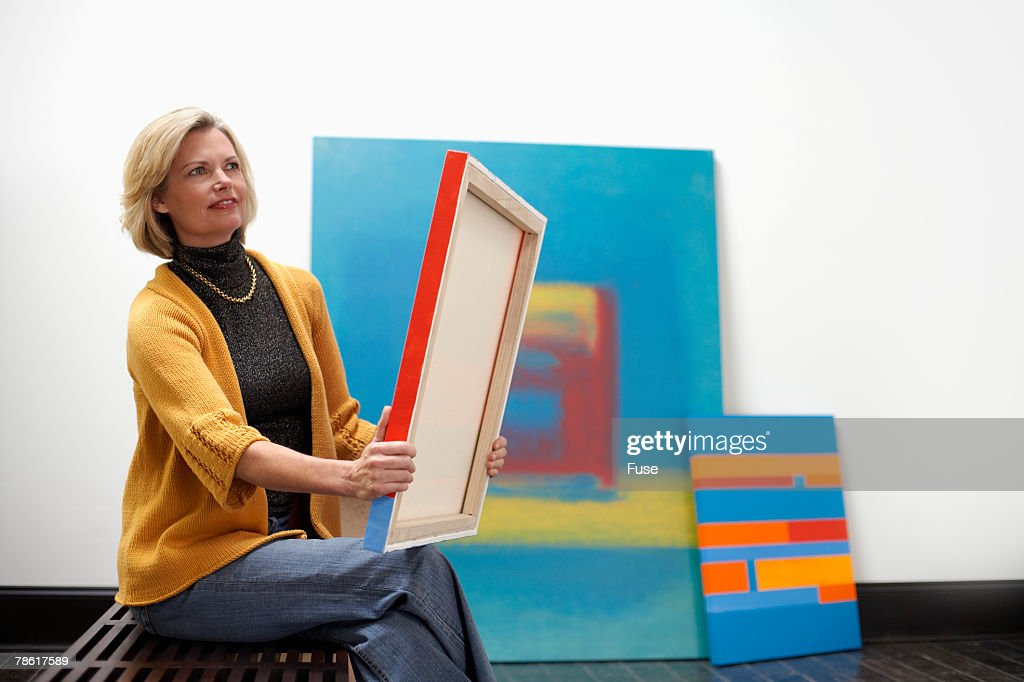 Artist Hanging Paintings at Exhibition : Stock Photo