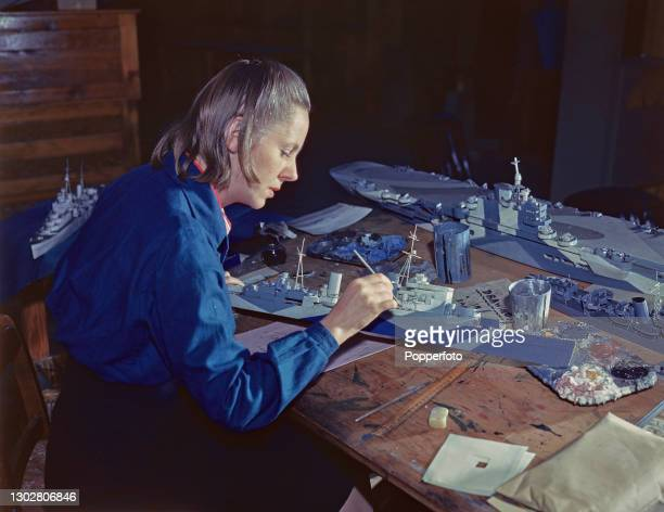 Artist Helen Collingwood paints a 1/16th scale model of a Royal Navy Minotaur-class cruiser with a camouflage design prior to testing in a tank at a...