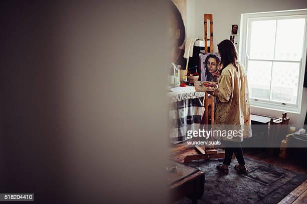 künstler im studio malen ein leinwand auf einer staffelei - künstleratelier stock-fotos und bilder