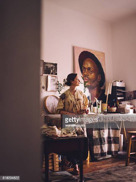 Artist in her studio with her art equipment thinking
