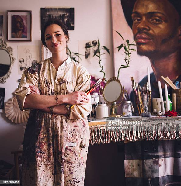Artist in smock standing with paintbrushes at her work table