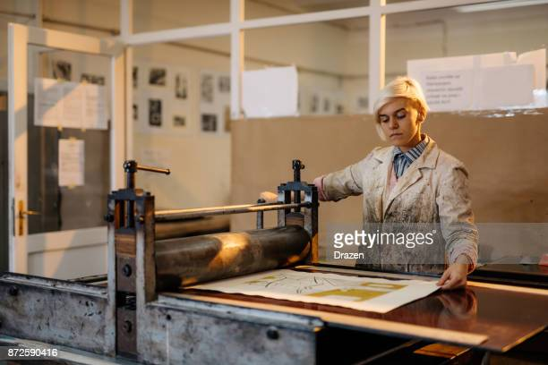 artist is producing artwork in her workshop with printing press and etching metal plate - intaglio stock pictures, royalty-free photos & images