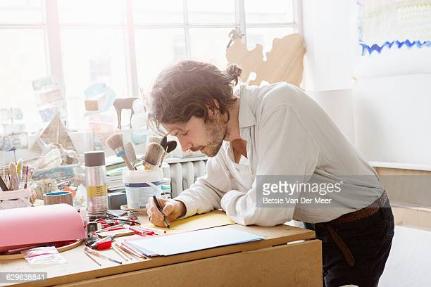 Artist is scetching in his studio.