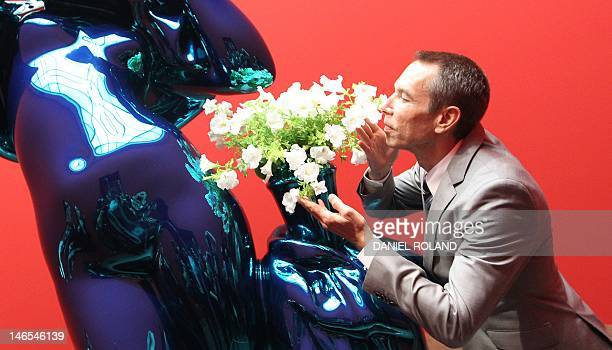US artist Jeff Koons poses for a photo in front of the sculpture Metallic Venus at the Liebighaus Skulpturen Sammlung during the opening of the...