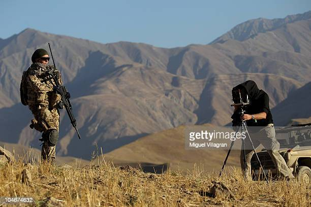 Artist Jo Roettgen takes a picture of a German Bundeswehr soldier patroling high ground with a Deardorff field camera on October 2 2010 in Feyzabad...