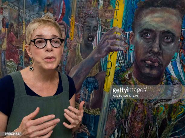 Artist Jodi Bonassi beside her artwork titled 'Monster on the Train' that highlights racial issues under President Trump during the Visual Artists...