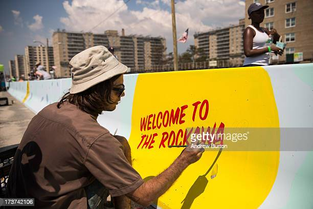 Artist John Garcia paints a mural along a roadway barrier on July 17, 2013 in the Rockaway neighborhood of the Queens borough of New York City. The...