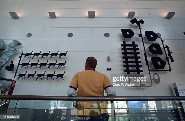 DENVER CO NOVEMBER 18 2004 Artist John McEnroe works on installing his 3 section 3dimensional wall sculpture 'Model State A Local Cosmology' in the...