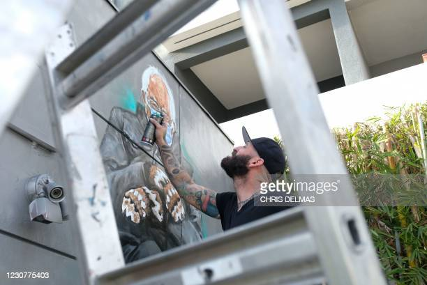 Artist Jonas Never applies finishing touches to his mural of Senator Bernie Sanders in Culver City, California on January 24, 2021. - Standing out in...