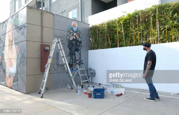 Artist Jonas Never looks at his finished mural of Senator Bernie Sanders in Culver City, California on January 24, 2021. - Standing out in a crowd of...
