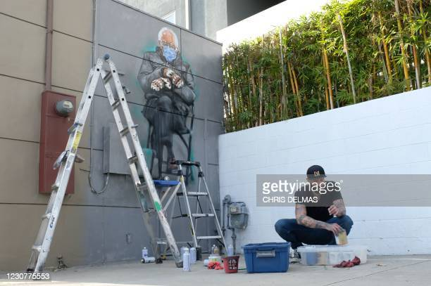 Artist Jonas Never packs his equipment after finishing painting a mural of Senator Bernie Sanders in Culver City, California on January 24, 2021. -...