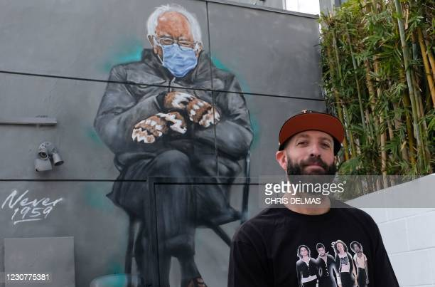 Artist Jonas Never poses in front of his finished mural of Senator Bernie Sanders in Culver City, California on January 24, 2021. - Standing out in a...
