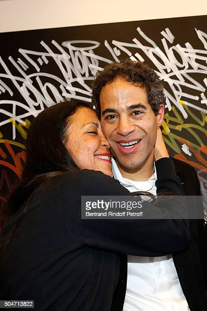 Artist JonOne and his wife Mai Lucas Perello pose in front of a work JonOne has just realized in Live during the Guerlain collaboration with Graffiti...