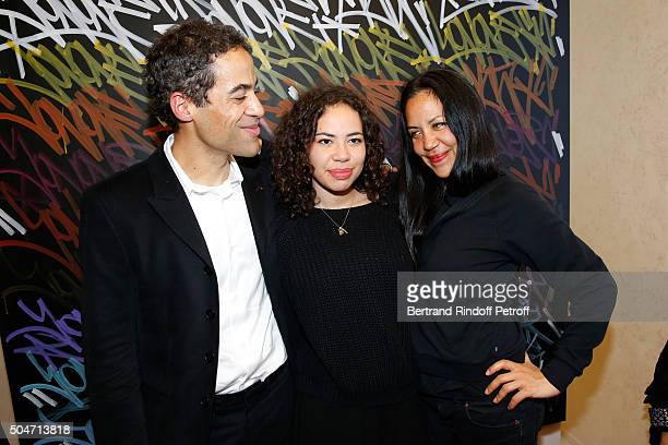 Artist JonOne his wife Mai Lucas Perello and their daughter Jaika pose in front of a work JonOne has just realized in Live during the Guerlain...