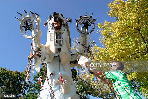 """Artist Joseph Gagnepain of Geneva, Illinois, makes some last minute adjustments to his """"Polar Scare"""" display during the Scarecrow Festival in St...."""