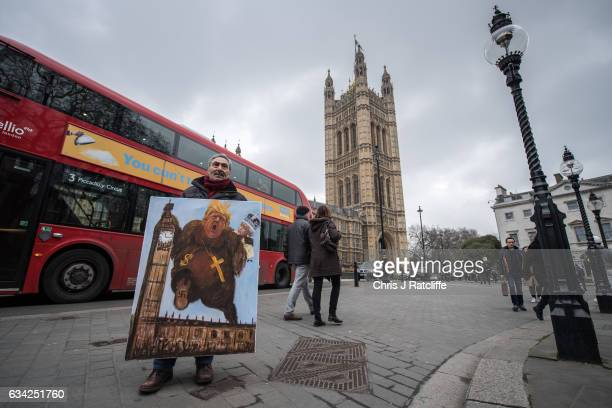 Artist Kaya Mar holds his latest political satire painting of Donald Trump depicted as King Kong with Queen Elizabeth II climbing Elizabeth Tower...
