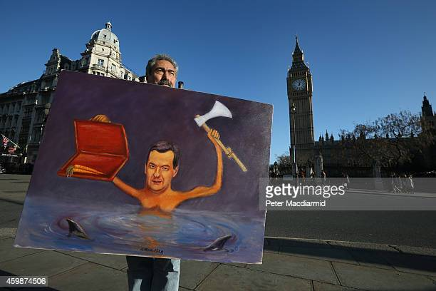 Artist Kaya Mar stands near Parliament with his cartoon painting depicting Chancellor of the Exchequer George Osborne waving an axe on December 3...
