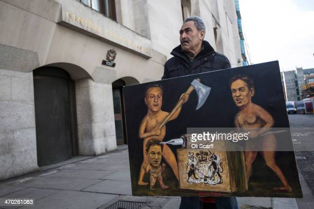 Artist Kaya Mar stands with his painting depicting David Cameron Ed Miliband and Nick Clegg challenging press freedom outside the Old Bailey on...