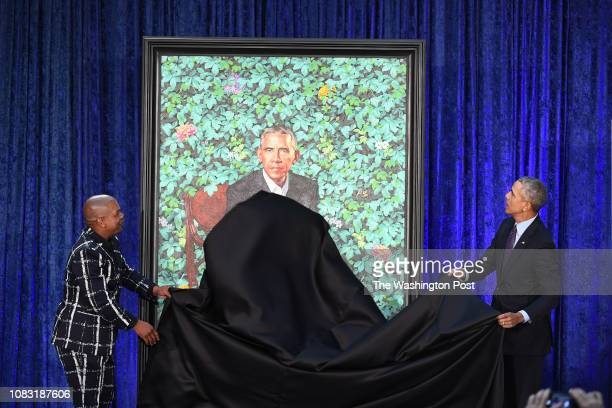 Artist Kehinde Wiley left and former President Barack Obama take a cloth from Obama's presidential portrait as he and former First Lady Michelle...