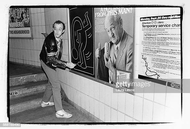 Artist Keith Haring drawing on a subway platform in New York City