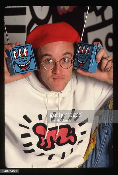 Artist Keith Haring holds two radios he designed at his Pop Shop