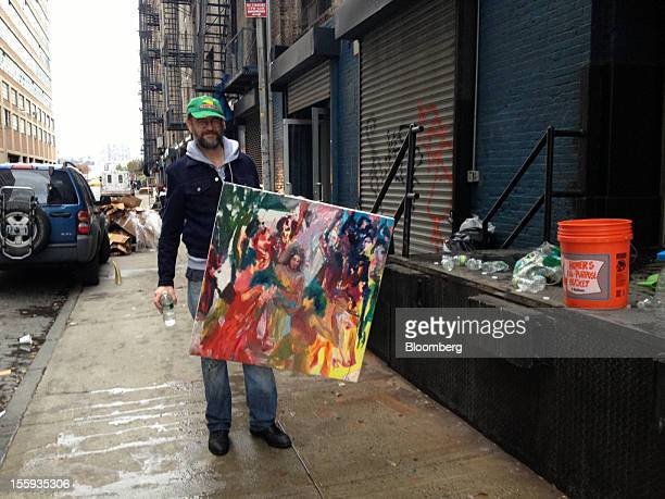 Artist Keith Mayerson stands for a photograph while holding one of his damaged painting outside of the Derek Eller gallery in New York US on Thursday...