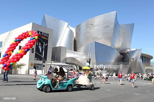 Artist Kenny Scharf and Zena Scharf tow artist Ann Magnuson as they drive there golf cart during the Trespass Parade through downtown Los Angeles and...